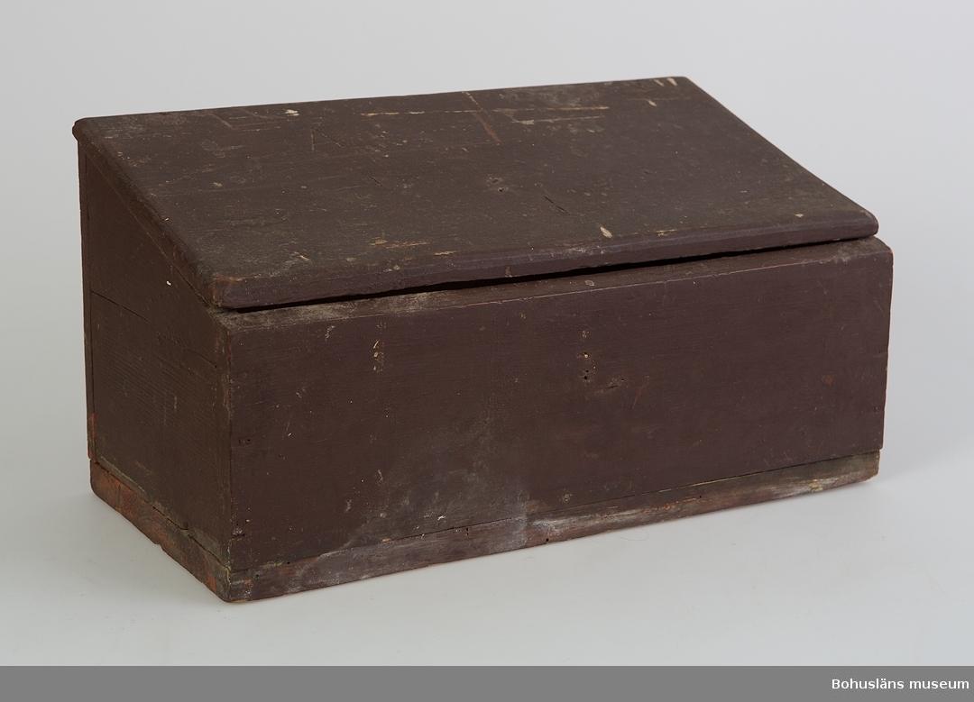 """Rektangulärt med pulpetlock. Locket är fäst med relativt moderna gångjärn. Täckmålat med brunlila färg, i nederkanten skymtar en (engelskt) röd, mager färg. På lockets ovansida och på framstycket finns hål efter märlor som fäst ett enkelt lås. På lockets ovansida är ett utskuret """"A"""". Även lockets insida är täckmålad. På den inre bakre långväggen är """"iordningsatt den 26/1 1894"""" skrivet i blyerts. I botten är rester av ljusröd färg av anilinfärgat papper. Mögelskador. Se Bilagepärmen UM19947.  Litteratur: Lychou, Kerstin, Hemslöjd & Folkkonst i Bohuslän, Warne förlag, Partille 1996."""
