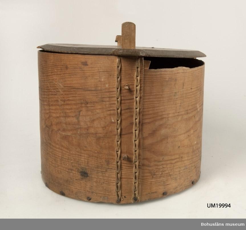 """Rester av adresslapp med text: """"Fr. GÖTEBORG"""" finns på locket som är tillverkat i ett stycke med ett handtag av snöre, tillverkat av lin. Knäpplåset består av ståndare som är fastsatta på insidan av svepet den ena är tappad och spikad, den andra spikad. Svepet är ihopsatt med rot vertikalt, bottenplattan är spikad fast i svepet. Skador finns på övre kanten av svepet och lockets kanter. Botten och tappar har torkskador.  Se bilaga i Bilagepärmen.  Inventerat 1997-10-16 AK."""