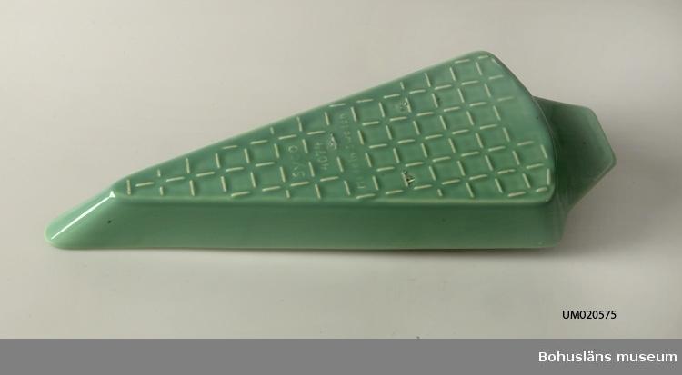 Triangelformad, ljust grönglaserad karott. Inpressad dekor längs mittlinje.  Märkt i botten med signatur i relief: SYCO 4074. Made in Sweden.