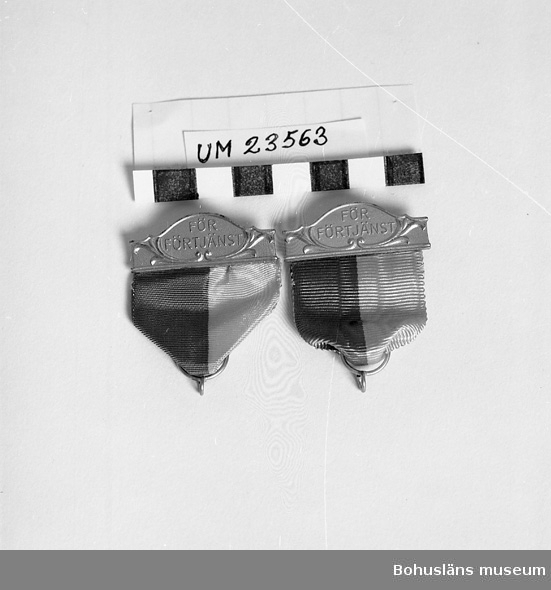 """471 Tillverkningstid 1950-1960 594 Landskap BOHUSLÄN  Blågult band med ögla nedtill för medalj.  Upptill skena i förgyllt silver med texten: """"För förtjänst"""". På baksidan silverstämpel samt nål. För guldmedalj. Förvarades i ask UM23560.  Jfr UM23561 och UM23562."""