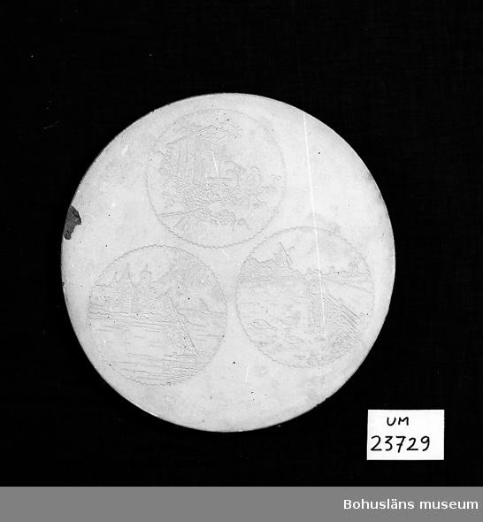 594 Landskap BOHUSLÄN  Ingraverat 3 cirklar med olika motiv. På undersidan oläslig oval stämpel. Samlingen med formar från Svenssons konditori omfattar UM16775 - UM16897, övriga föremål  UM23716 - UM23736, UM23751 - UM23753.