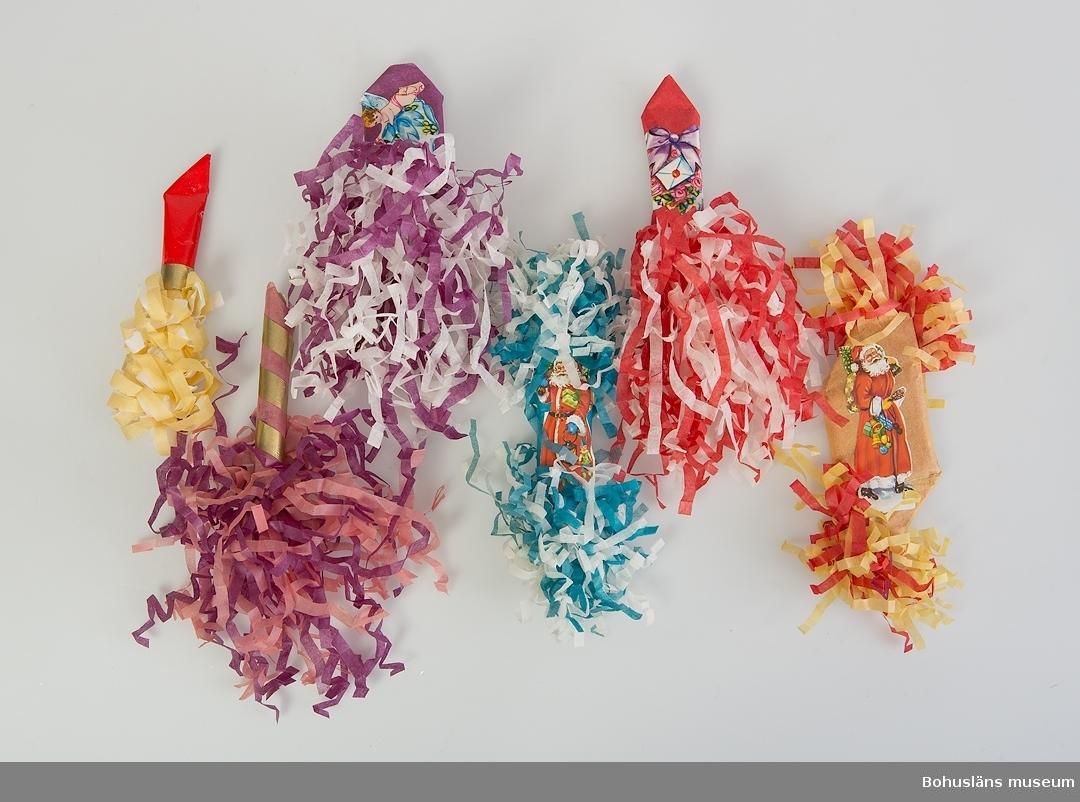 1 st röd och vit. 1 st lila och vit, 1 st gul, röd, vit, 1 st gul och röd, 1 st turkos och vit, 1 st rosa och lila. Veckat silkespapper. På fyra av julgranskaramellerna sitter bokmärken fastklistrade. På de två övriga är det dekoration av guldpapper.
