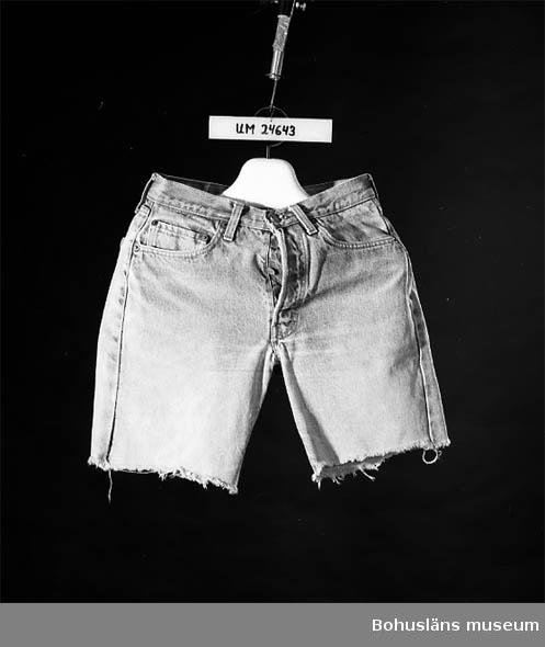 """594 Landskap BOHUSLÄN 503 Kön KVINNA 414 SAMT (OTYDLIGT) """"R"""" INSKRIVET I EN CIRKEL  Ljust blå jeans avklippta till shorts med ca 20 cm långa ben. Ofållade. Med jeansskärning: Fram iskurna fickor med rundade öppningar samt en mindre ficka (myntficka) fastsydd på högra sidans fickskylt, bak snedskuren besparing upptill och utanpåfickor. Knäppning fram med metallknappar (fyra i gylfen, en i linningen). Linning med hällor. På knapparna inpräglad text: """"LEVI STRAUSS & CO * S.F. CAL *"""". Dubbla stickningar (""""jeansstickningar"""") vid flera sömmar. Sex metallnitar vid fickorna fram som förstärkning. Bak rött tygmärke med tryckt vit text (se Märkning ovan.) Vid linningen bak en ljusbrun pappersetikett (ska imitera läder) med otydlig röd text. Röd etikett visar troligen att jeansen är tillverkade i USA. Använda som klädsel vid servering på Havsbadsrestaurangen i Lysekil, Bohuslän.   Insamlade i samband med dokumentation av Havsbadsrestaurangen, Lysekil, sommarsäsongen 1991. Se museets arkiv.  Slitna, speciellt vid innerbensömmarna. Gulnade (smutsiga?) upptill.  Litt: Wintzell, Inga, Jeans och jeanskultur, Uddevalla 1985, s. 94-127 (kulturhistoriskt om jeans på 70-talet). Omkatalogiserat 1997-10-02 VBT"""