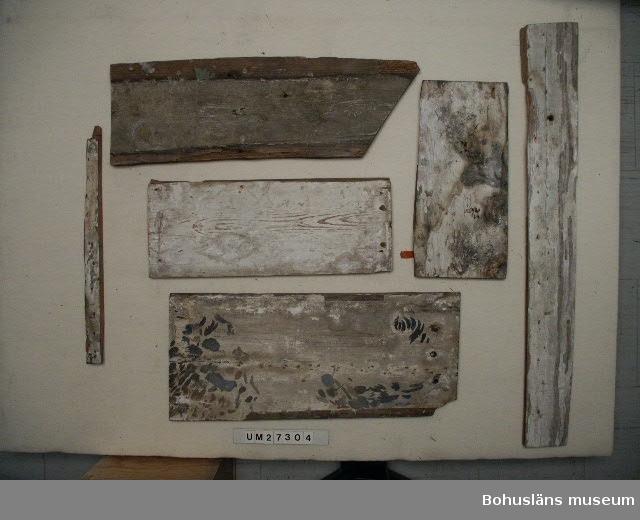 """Tolv dekormålade panelbrädor från 1600-talets senare del till 1700-talets första hälft. Brädorna har troligen proveniens till byggnad tillhörig Rutger von Ascheberg. De kraftiga brädorna är av olika längd och utgör del av en tak- eller väggpanel. Det som återstår verkar vara ett hörnparti som består av brädorna UM27304:1 - 10 och antyder att hela motivet bör ha varit kvadratiskt eller rektangulärt. Större delen av panelen saknas således. Ytterligare sex delar finns som inte passar till något annat, varav två har rester av dekormåleri, totalt 16 delar. Målningen är utförd i limfärg eller tempera i olika grå, röda och vita nyanser direkt på underlaget. Stilen är livfull barock. Motivet föreställer en kerub med uppfällda vingar. Ovanför figuren böljar ett bladornament på ömse sidor med en sköld med pärlstavsram och flerkantiga sidoflanker dekorerade med blomblad.  Brädorna är av olika längd och har kraftiga hål i ändarna efter handsmidd spik. Motivets  avslut mot vägg- eller taklist markeras tydligt av en kantlinje i målningen, spikhål och brädornas omålade yttersta ändar.  Brädorna har senast suttit på andra våningen i villan """"Slottet"""" eller""""Petris pensionat"""" på Stenungsön. Huset är byggt på 1890-talet och uppfört på samma plats där Rutger von Aschebergs (1621 - 1693) jaktslott tidigare låg. Brädorna hittades av givaren-husägaren i samband med en badrumsrenovering 1965 och de bröts loss ur olika väggar. De satt då lodrätt spikade på reglar med målningen vänd inåt. Givaren försökte intressera någon kulturmyndighet för brädorna, men """"ingen vill ha dem"""". När givaren sålde huset på Stenungsön och flyttade1966 togs panelen med.  Möjligheten finns att denna panel tidigare suttit i det Aschebergska jaktslottet och i samband med rivningen på 1890-talet betraktats som rivningsmaterial som kunnat återanvändas som väggpanel i den nya byggnaden.  Stenungsön ingick som donationsgods till Rutger von Ascheberg efter försvenskningen av Bohuslän 1658. Han lät här uppföra Aschebergska """
