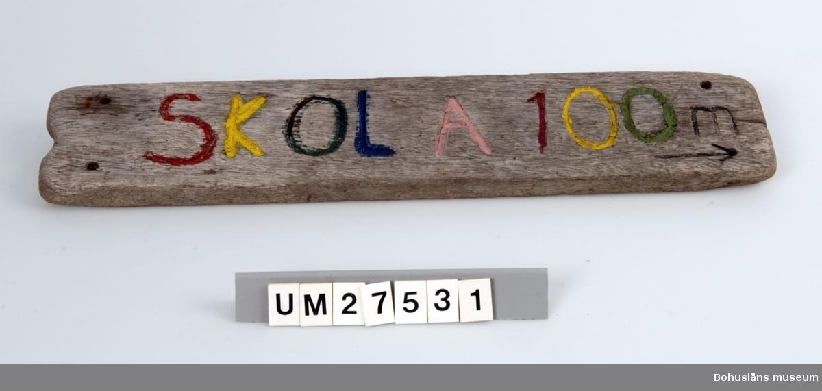 Vägskylt tillverkad av elev vid Åstols skola, Tjörns kommun. Vägskylt tillverkad av en bit drivved. På framsidan inhuggna texten SKOLA 100 m, målat i blått, rött , gult och grönt samt en pil som pekar åt höger.  Borrhål för skruvar.  Föremålet visades i utställningen Moderna skärgårdsbor på Bohusläns museum 2002. Utställningstext: Vägskyltar Nio skyltar som vägvisare på Åstol. Från affären till rökeriet är det 375 meter och från skolan till badplatsen är det 200 meter. Skyltarna berättar om en liten ö med många mötesplatser. Här finns affär, bibliotek och skola - restaurang, lekpark och flera församlingar. En tätbebyggd ö omgiven av havet, med skolan i centrum - så viktig för barnfamiljerna och åretruntboendet. Skyltarna är gjorda av elever i årkurs 4 - 6 på Åstols skola.  Skylten ingår i insamlingen i projektet Moderna skärgårdsbor, UM27511 - UM27595 och kommer från Åstol.  För övrigt material från Åstol, se UM27524-UM27538 och UM27566-UM27594; UM27524 Tjörn Runt-teckning UM27525- Vägskyltar, 9 st UM27533 UM27534:1-2 Eternitplattor, 2 vita refflade  UM27535 Eternitplatta, 1 vitmålad slät UM27536:1-2 Eternitplatta, 2 gröna UM27537 Cykelkärra UM27538 Matjordsäck, 2 st (omärkt) UM27566- 28 barnteckningar över Åstol, indiv. inv.nr. UM27593 UM27594 Skylt frikyrkan med gudstjänstaffisch Arkivet 9 uppsatser från skolbarnen i samband med teckningarna.  För information om projektet Moderna Skärgårdsbor, se UM27511.  Litt: Sjöholm, Carina. Moderna skärgårdsbor i gammal kultur. Skrifter utgivna av Bohusläns museum och Bohusläns hembygdsförbund nr 73. Bohusläns museums förlag.  Avsnittet om Åstol s. 17 - 45..