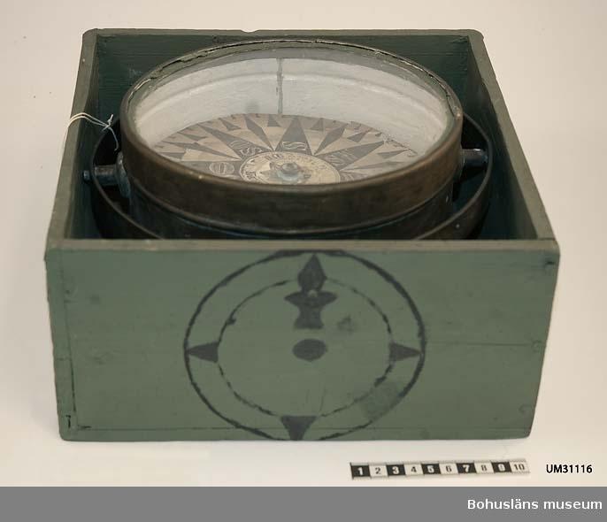 Kardanupphängd luftkompass i kvadratisk grönmålad låda. Lådan är möjligen tillverkad senare.  Spikade hörnen. Lådan saknar skjutlock, vilket kompasslådor av denna typ brukar ha. Kompass av mässing med glasskiva. Kompasskiva av vitt papper med kompassros i svart tryck, fuktskadad, oläslig text.  G. RAM...LERN.. Rosen graderad i fyra sektorer 0-90 grader. Väderstrecken märkta: Styrstreck i form av en vasakärve (?) betecknande N,  NW, W, SW, S, SO och NO. Kompasskivan hänger i kompasskålen på ett stift.   Lådans bemålning liksom kompassens vita invändiga bemålning troligen gjord samtidigt. Korroderad.  För ytterligare upplysningar om Carl Gustaf Bernhardson samt om förvärvet, se UM31100.