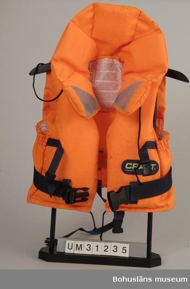 Föremålet visas i basutställningen Kustland,  Bohusläns museum, Uddevalla.  Flytväst för barn 15-20 kilo. Västmodell i orange nylontyg med kraftig krage. Flytelemen på framstyckena och i kragen. Två mörkblå nylonslejfar med mörkblå  plastspännen för knäppning runt magen och likadan nyonslejf för säkerhetsknäppning mellan benen. Blå snörknäppning i halsen. Reflexer fastsydda på kragens framsidor. Mörkblå gummidekal på vänster framsida med texten: CRAFT nautical Etiketter fastsydda inuti  med säkerhetsinstuktioner på flera språk och uppgifter om bärighet och storlek samt skötselanvisningar. Svarta mögelfläckar.
