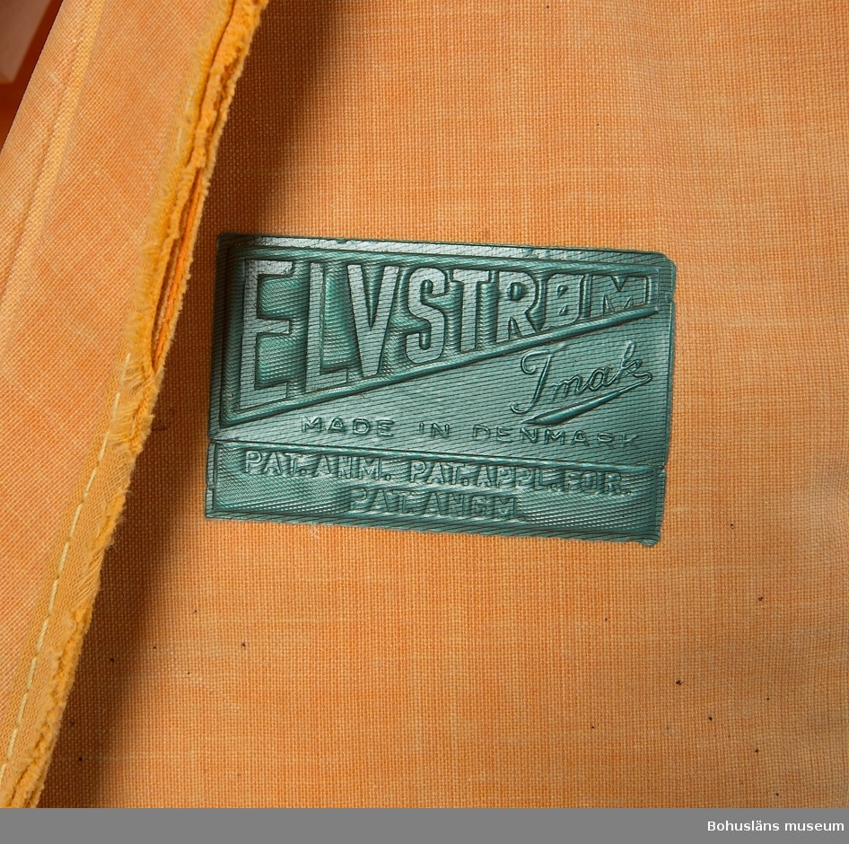 """Seglarväst utan krage av orange plastat tättvävt tyg. Bakstycket och de två framstyckena fästade i varandra med nylonlina som löper i små, glest placerade öljetter. Stängs framtill på två ställen med större oljetter där den ursprungliga knappen av plast  sitter kvar upptill, undertill en provisorisk tamp. På framsidan grön (tidigare blå) etikett med präglade texten: """"ELVSTRÖM Imak MADE IN DENMARK"""" Patenterad modell."""