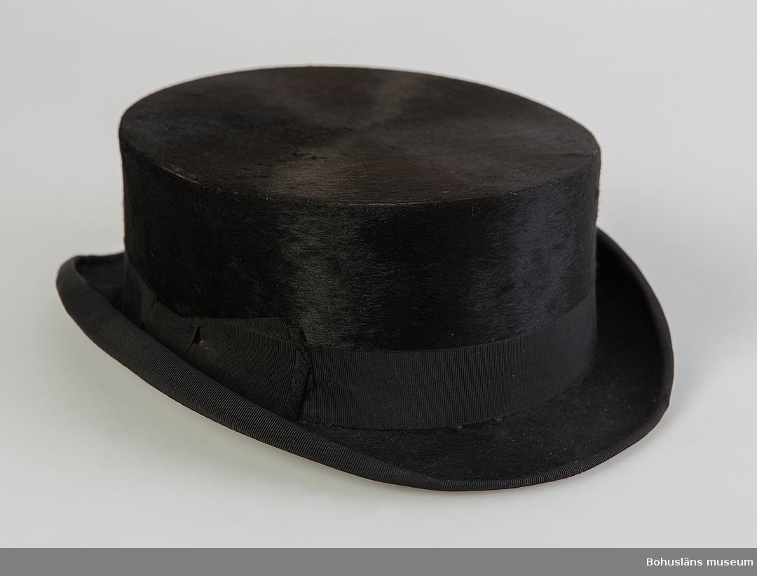 """Svart hatt med litet brätte och platt kulle. Gummisnodd (betydande skador) för att hålla hatten på plats. Det tunnare ylletyget på brättets undersida (troligen brätte av papp) har skadats av insekter. Kullen är täckt av ett plyschtyg där luggen borstats så stråna ligger platt i en riktning. Ripsband runt brättet samt som dekor runt kullen. Nersydd rosett av bandet vid ena sidan. Inuti kullen ljust beige bomullstyg med stämplad information. Bild med krönta sköldar och lejon samt textband: """"JNCROYABLE"""". """"Hjalmar Larsson Uddevalla."""" tryckt under beskrivna bild. Svartfärgat tunt skinn på kullens insida. Del av riddräkt UM62.04.001 - UM62.04.007  Mer information se UM62.04.001"""