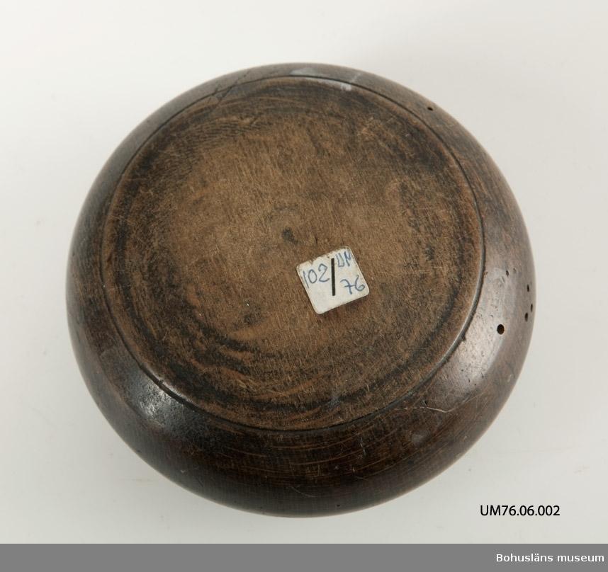 Rund, svarvad med lock. Locket har en rektangulär knopp mittpå. Locket låses med en vridanordning där två skurna streck visar när den är öppningsbar. Locket har en något upphöjd spegel på mitten. Betsad. Något skadedjursangrepp.  Litteratur: Nylén, Anna-Maja, Hemslöjd, Håkan Ohlssons förlag, Lund, 1978, s. 345-349.  Ur punktnummerkatalogen 1958-1976: J. H. Ohlsson, Uddevalla Dosa, rund, svarvad Diam. 10,5 cm, h. 5,5 cm.
