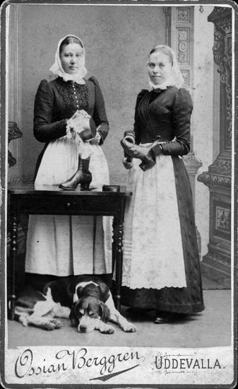 Ateljéporträtt av två kvinnor som putsar ett kokkärl respektive ett par skor, under bordet ligger en hund
