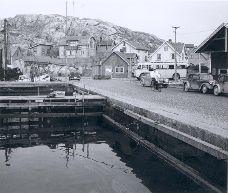 """Noterat på kortet: """"Gravarne Bäckevikstorget ca. 1950. Byggn. närmast till v. om bussen är den nu (1959) nedrivna brandstationen""""."""
