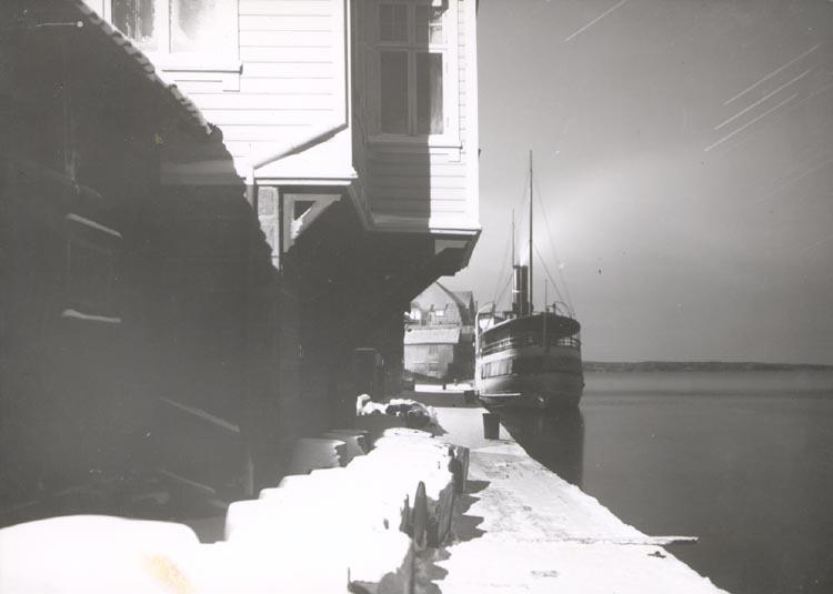"""Noterat på kortet: """"SMÖGEN"""". """"S/S """"BOHUSLÄN"""" ÖVERNATTAR I SMÖGEN EN VINTERNATT 1923"""". """"FOTO(B57) DAN SAMUELSON 1924. KÖPT AV DENS. DEC. 1958""""."""