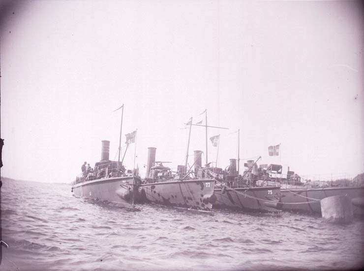 "Enligt text som medföljde bilden: ""Svenske Torpedbåtarne Nr 5,-71,-75,-77 (Freke, Bygve, Agne, Agda) från bogen vid bojen 20/8 1899. Lysekil""."