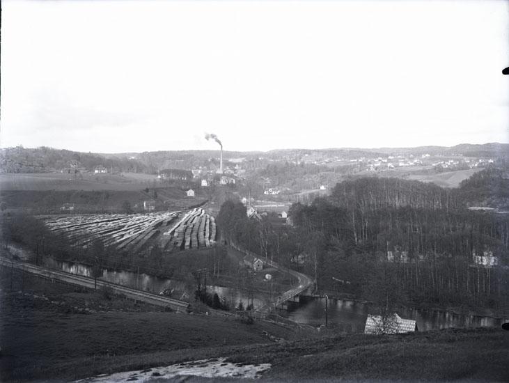 """""""1931. nr. 40. 1. 12 sek. med papper över en lampa. Bohusbanan i förgrunden, Munkedals fabrik i bakgrunden.""""  """"Örekilsälven. Bohusbanan. Bruksvägen. Tången-bron."""""""