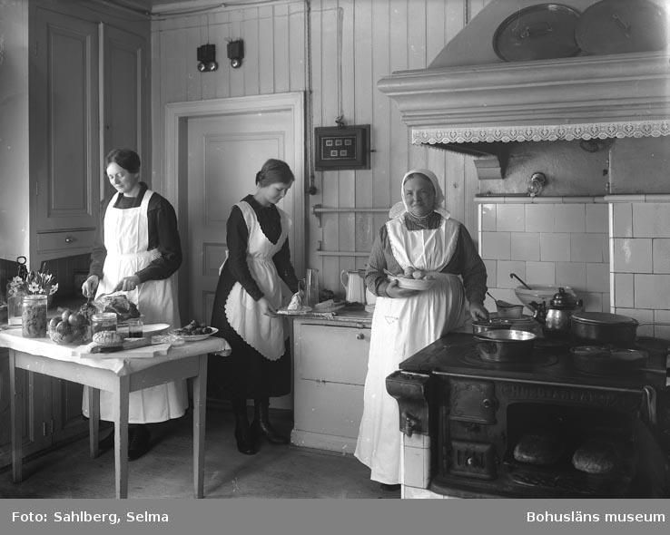 """Enligt medföljande noteringar: """"105. Mässens kök. Fröken Ida Larsson med medhjälpare."""""""