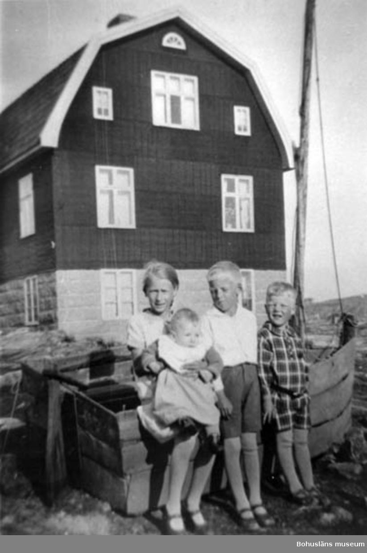 """Enligt text på fotot: """"Kalle på Sluttets hus och hans barn/Smögen Fr.v. Karin-Ingvar-Tore och lille Gunnar Karlsson taget omkring 1930, alltså 60 år 1990 OBS båten de står och lutar sig emot""""."""