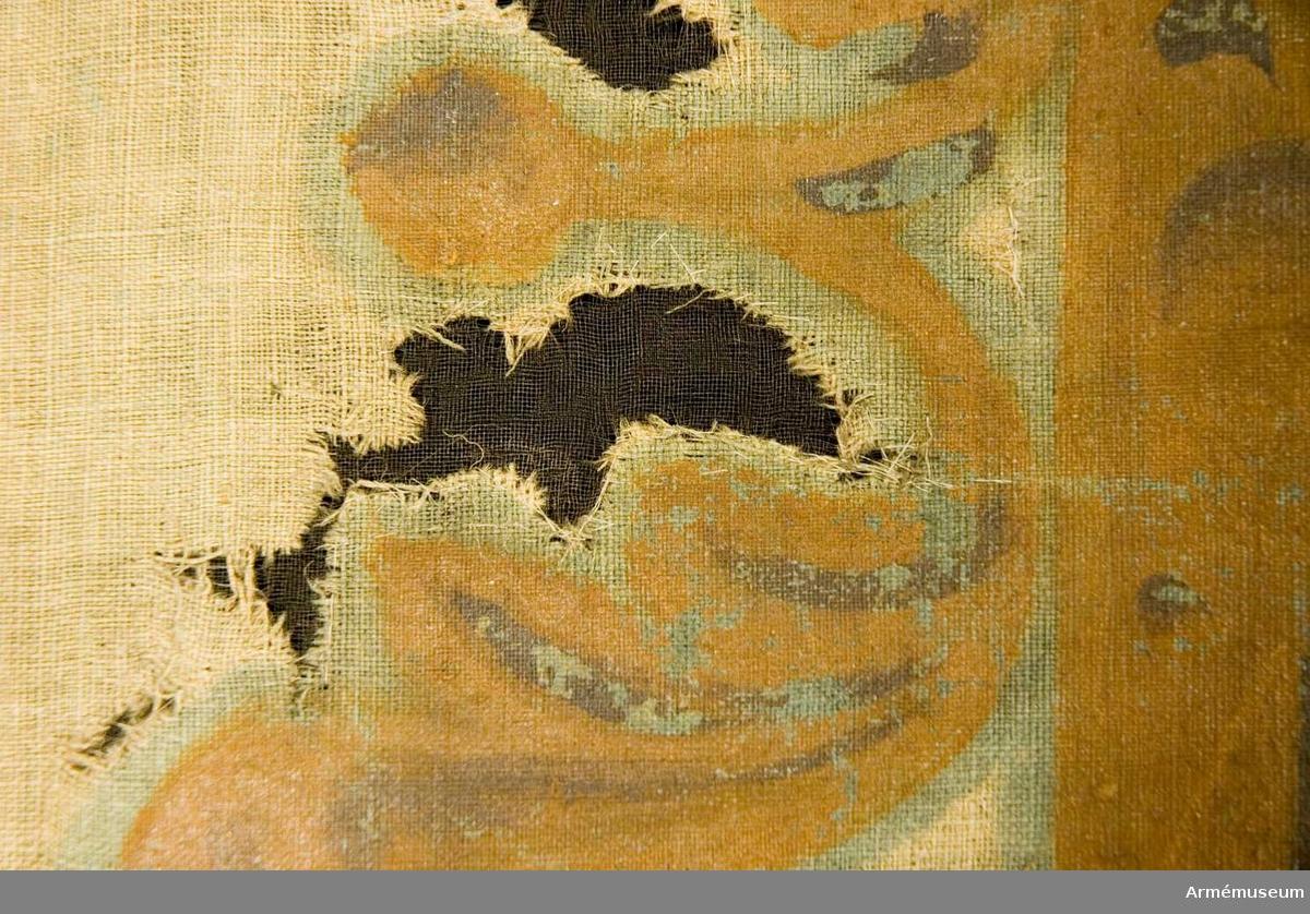 Grupp B.  Uppbådsfana för Mjöbäcks och Sexdräga socknar. Kinds härad. Västergötland. Fanduk av blått lärft, hopsydd av två längder, med målade  emblem, lika på båda sidor: en av en öppen krona i gult krönt sköld nedtill med två korslagda av band med tofsar hopknutna palmkvistar målade i brunt. I skölden ett K rikt utsirat. Därovan band med inskription. På ena sidan Kiendz Härads vapen. På andra sidan Miöbeka och Sexdräga Compagnie. Fastspikad med linneband och kupiga mässingsstift. Stång av brunmålad furu. Spets av mässing. Holken 100 mm lång.