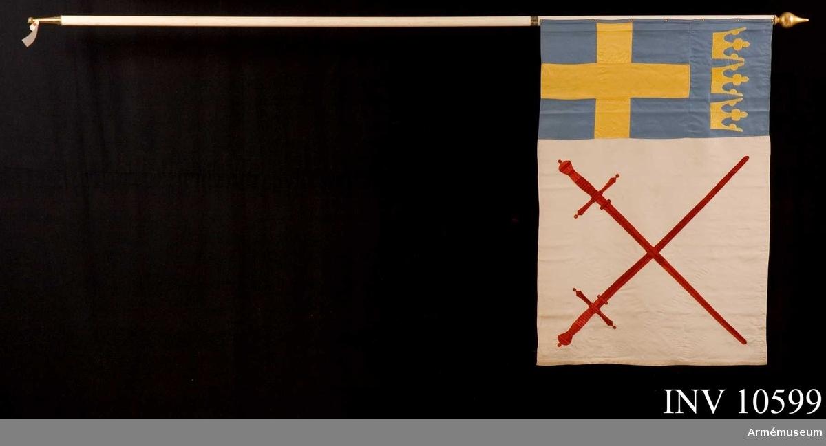 Grupp B I. Ytterst på vit sidenbotten två broderade korslagda värjor. På det inre blå fältet ett gult kors med tre öppna kronor över.  På stången silverplatta med inskription: 'Stockholms Landstormsförbund Indenturavdelning Tioårsjubileet 19-9-1936. Gåva av Landstormslöjtnant T. Hedelius.'.