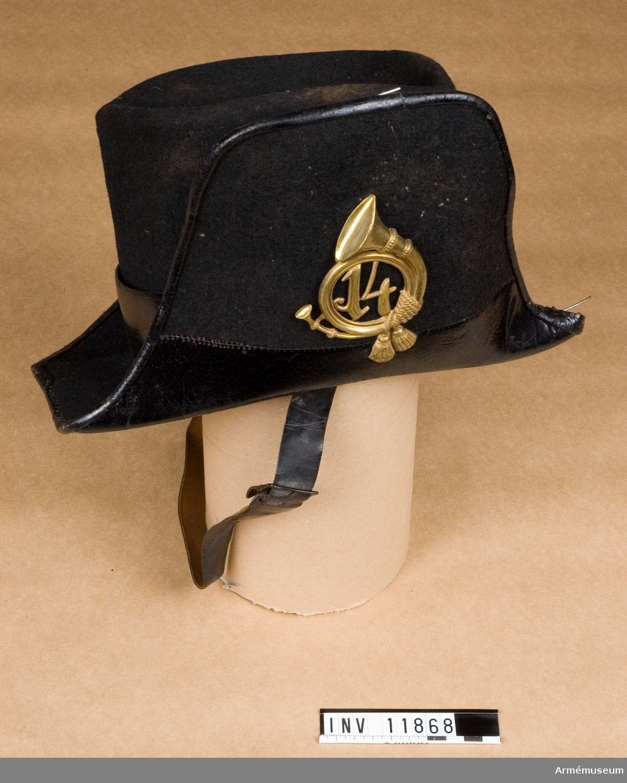 """Grupp C I. Hatt för postiljon.  På sidan ett posthorn med små tofsar - av metall? - och inskrivet i den av hornet bildade cirkeln siffrorna """"14""""."""
