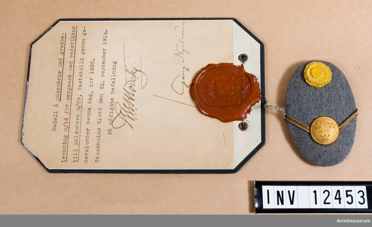 Grupp C I. Modell på mössmärke med gradbeteckning m/1914 för sergeant med vederlikar till pälsmössa m/1909.  Från intendenturens modellkammare.