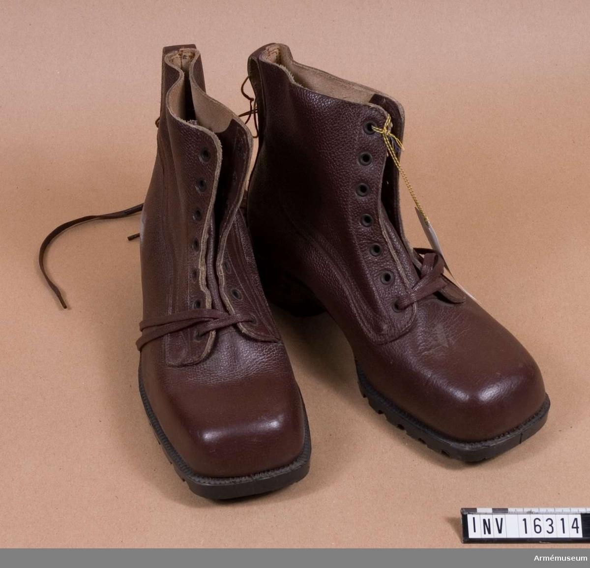 Av brunt läder, med snörning och kraftig gummisula. Urtag i klacken för skidbindning. Storlek 43.