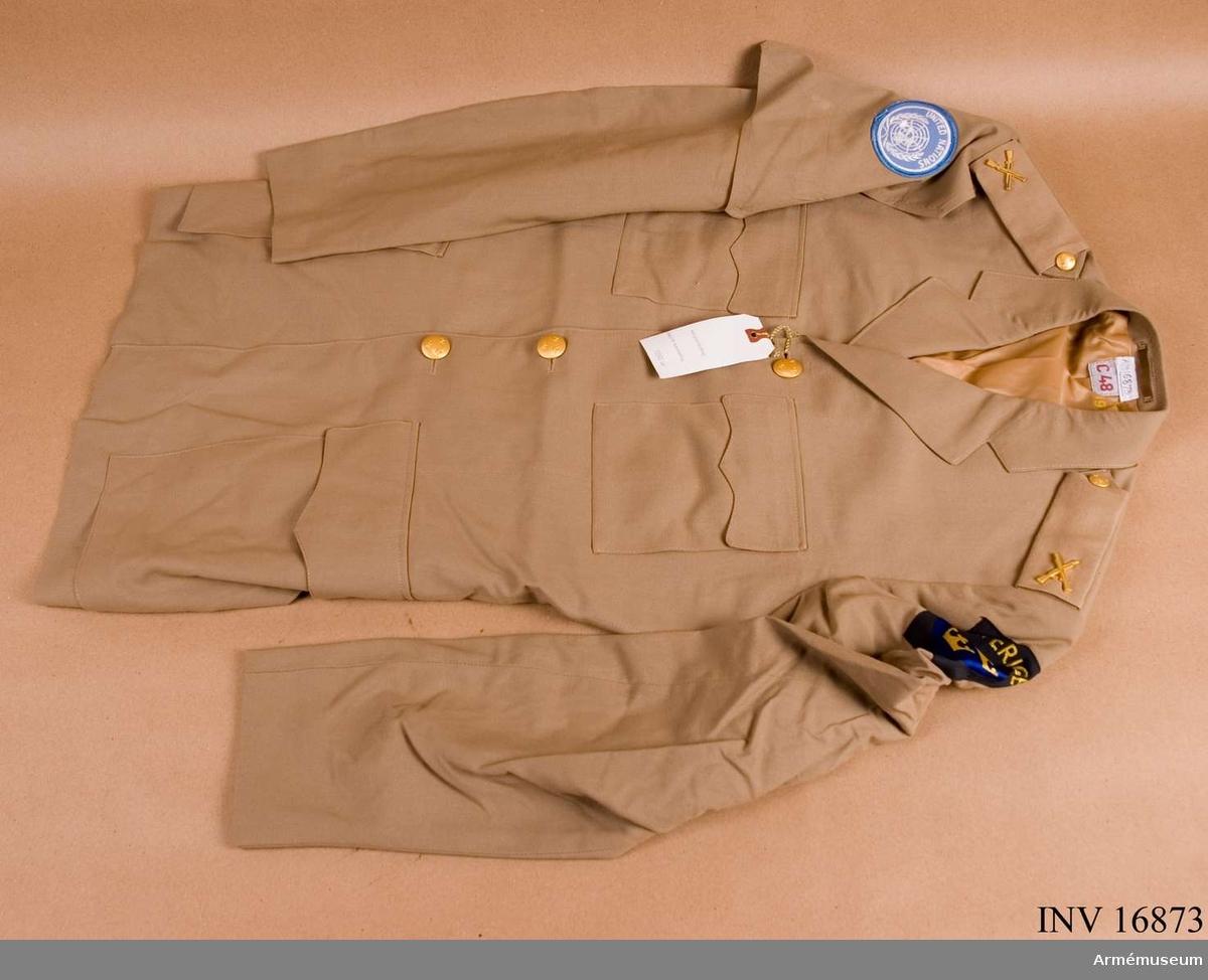 Stl C 48. Av beigefärgat tyg. Enradig och knäppt med fyra knappar. Påstickade fickor, bröst- och sid-, med ficklock samt fasta axelklaffar. Hylsor trädda över axelklaffarna med tecknet för infanteriet i guld. Axelklaffen är knäppt med trekronors-knapp modell mindre, i guld. Sprund bak. På H ärm en ärmhylsa, s k arm-let, av vapenrockens tyg med FN-emblemet och på den V överärmen nationsmärket för militär personal i utlandet. Två innerfickor varav den ena bär en etikett från Jelm Excl- sive, made by Jelm division -Sweden.