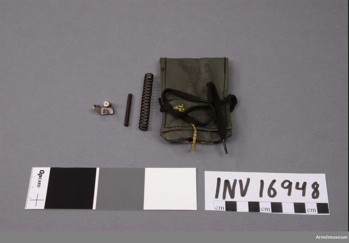 """Kaliber 6,5 mm. Påse av plastväv. Märkt """"0010 6,5"""". Består av: 1 reservdelspåse, 1 utdragare, 1 matarfjäder, 1 tändstiftsfjäder."""