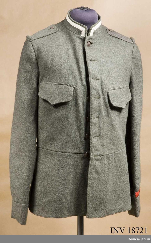 """Grupp C I. Ur uniform för trumpetare vid kavalleri, Holland. Av fältgrönt kläde. Enradig med 7 knappar. Åtsittande med tvärsöm i midjan. I ryggsömmarna finns två vapenprydda bältkrokar och på sidorna två krokar för livrem. Axelklaffar av samma gröna tyg fastsydda på rocken, l:110 mm, b:45 mm, med knapp på sidan (mindre modell), fastsydda bak och överklädd med samma kläde. Fickor, 2 på bröstet. Ficklock med avrundade hörn, i mitten utdragna till en spets. Foder av grått bomullstyg med inre sidoficka """"M A,"""" """"1918"""",  """"S W"""", """"C"""". Knappar av brons med statsvapnet (krönta lejon) på bröstet vid knäppningen 7 st, d:20 mm, på axlarna 2 st, d:15 mm. Krage upprättstående med raka vinklar med vita bomullsband, 15 mm bred (utmärkelsetecken för trumpetare). Foder av samma kläde. Krage har stor hyska och hake. Ärmuppslag av samma kläde. 7 cm höga, rakskurna. På ärmuppslag finns märken av rött kläde:  """"Flammande Granaten"""" för """"Korporaal vuurwerker"""" (korporal feuerwerker) =fyrverkarkorpral. Två signalflaggor i kors signalmärken för korpral och soldat; Stjärna i krans för """"scherpschutter I.e klass"""" - skarpskytte- märken för 1:a klass soldat; Vimpel av röda  bomullsband, b: 20 mm, h:190 mm, """"Preiwilliger 1:a klasse"""" frivillig första klass husar. LITT  Handbuch der Uniformkunde. Prof. Richard Knötel, Hamburg 1937. Sida 256. """"Die graue Felduniform ihre Waffen Rangab- zeichen"""". År 1912 infördes i holländska armén fältgrå uniform. Fullständig beskrivning av vapenrock med 7 knappar och  upprättstående krage. Efter tabel av överste Hartman  (Legar Museum, Leyden). gradbeteckningar: 1 ) stjärna femuddig kläde för korpraler och soldater, skarpsyttmärke, 2 ) två signalflagor i kora av rött kläde för korpraler och  soldater signalmärken,3) flammande granater av rött kläde för fyrverkar korpraler, 4) vimpel av röda band frillig första klass. Efter tabellen """"Uniform der Hollandische Cavalarie"""" bild """"Huzaar i Klasse"""" (trumpetare) i samma vapenrock med vita band vid kragens övre kant. Stjärna i kra"""