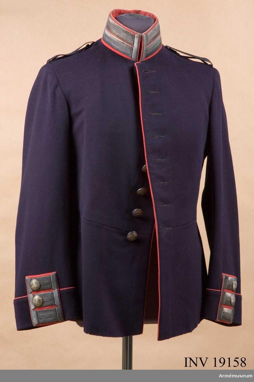 Sydd av mörkblått kläde med röd krage och passpoaler med silvergalon och silverknappar (tillverkade Sporrong). Rött foder med på insidan av innerfickan en etikett från MEA Militärekiperings A.B. Stockholm den 18/7 1922. Löjtnant S. Kinmansson.