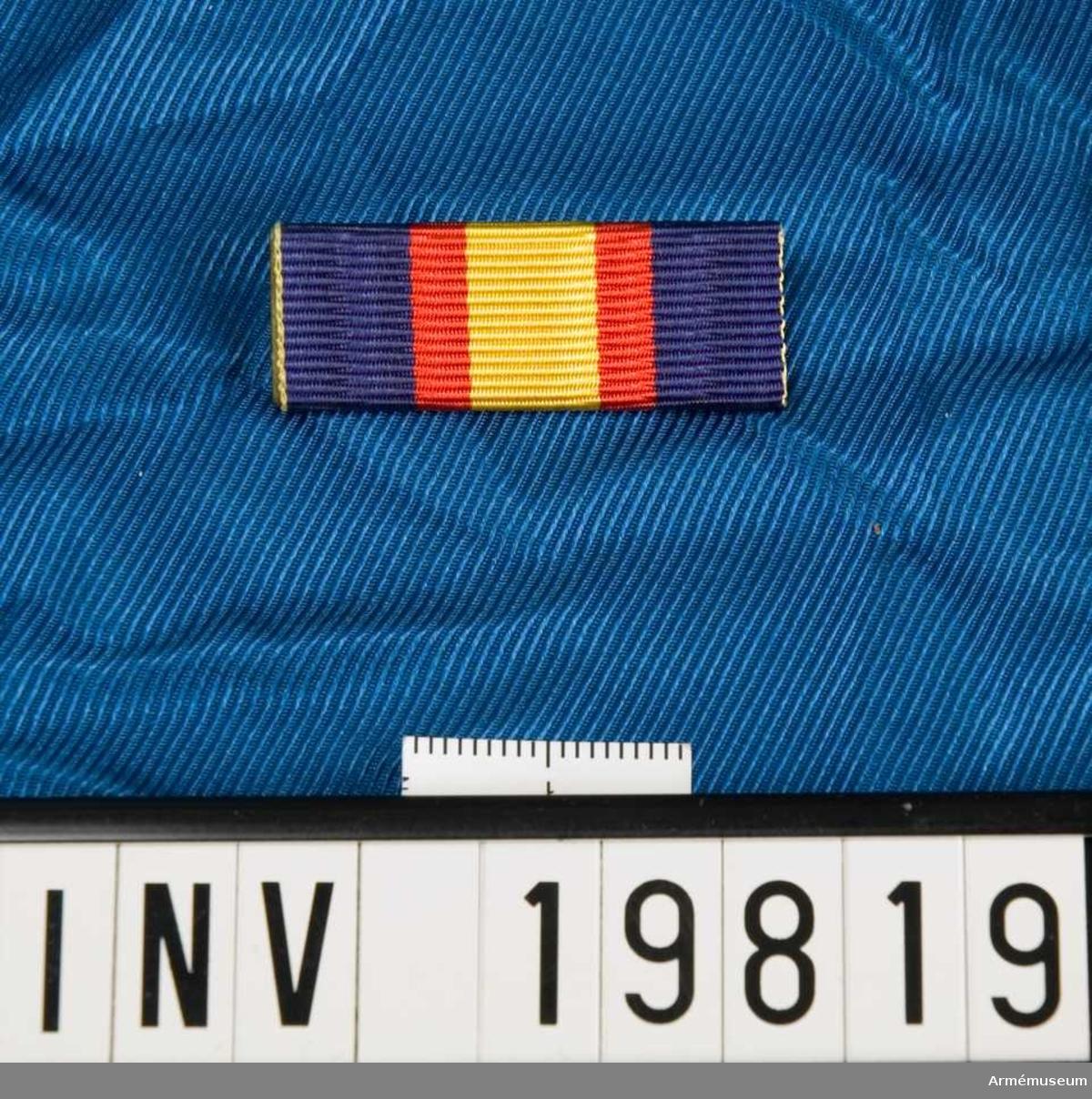 Blått band med en bred gul rand på mitten åtföljd av en röd rand på vardera sidan. Släpspännet förvaras i en ask tillsammans med en medalj och en miniatyrmedalj.