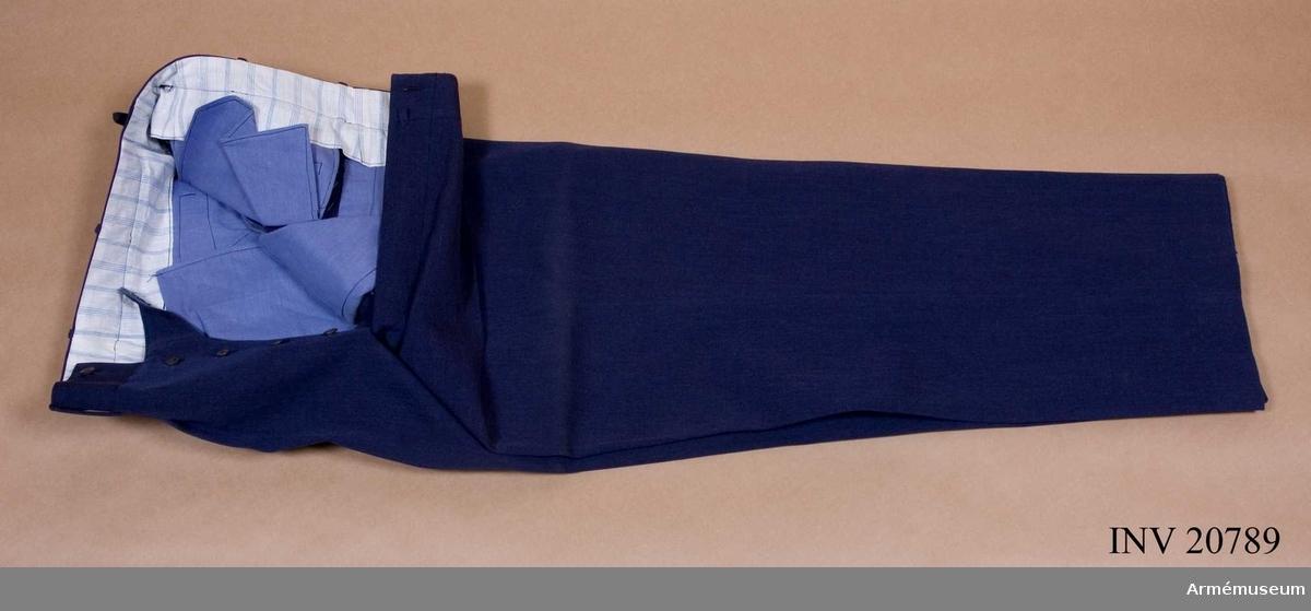 Grupp C I. Av blågrått kläde. Fyra fickor med treuddiga lock och knappar. Knappar av ben. Foder av blårandigt tyg.