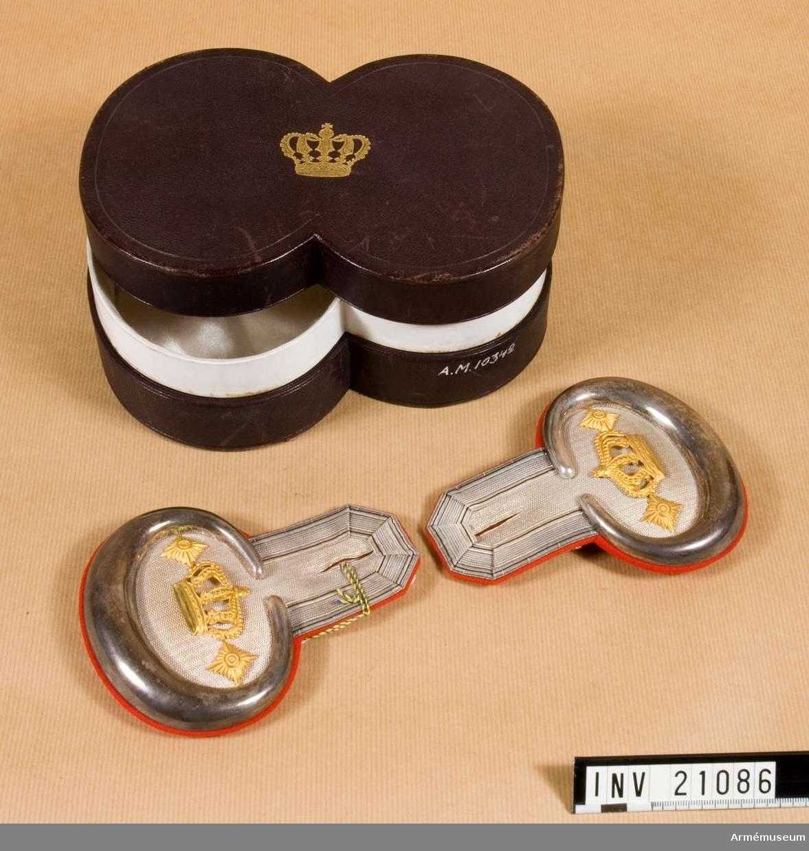 Grupp C I. Ur uniform för officer vid Badisches Leibgrenadierregiment. Består av kappor, kolletter, syrtut, vapenrock, ridbyxa, långbyxor, hjälm, mössa, skärp, sabel m tillbehör.Epåletter med frans. Av vävd silvermatta och silverplåt. De har silverbuljon och är fodrade med rött kläde.. På epåletterna finns en krona av förgylld metall men inga stjärnor =majors grad. Buljon =stabsofficers rang.