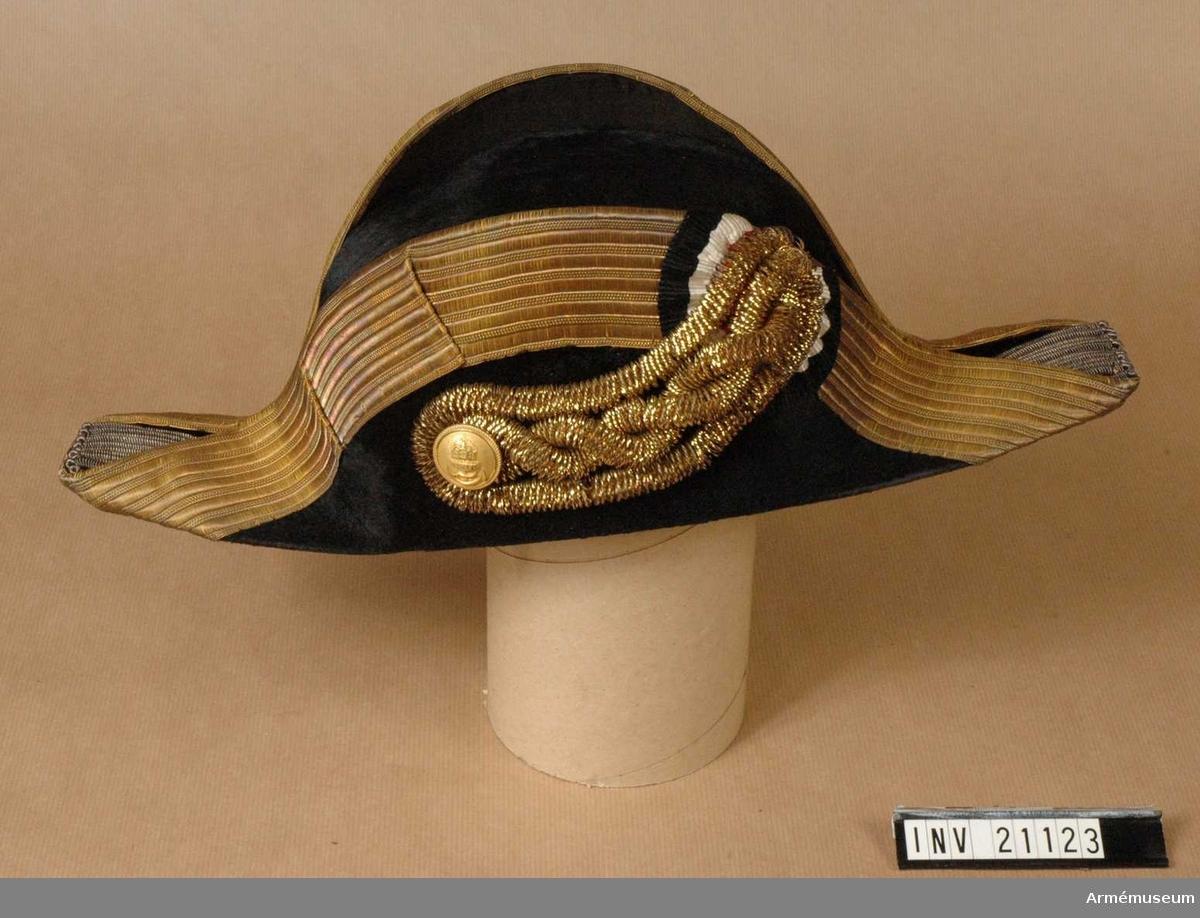 """Grupp C II. Ur uniform för gala för konteramiral i tyska flottan. Av svart siden filt (?), trekantig. Foder av ljust läder och vitt siden. På fodret påskrift """"Wassenhaus für Armee und Marine, Berlin"""", och krona med bokstav """"G"""". Galon, b:50 mm, av guld kantar hatten. Tofsar av guldbuljon, b:50 mm, vid hattens ändar. Tecknet på H sida av hatten är av guldbuljon, b:55 mm, med stor ankarknopp av guld och kokard av sidenband med tyska nationalfärgerna svart, vit, röd. Enl W Granberg."""