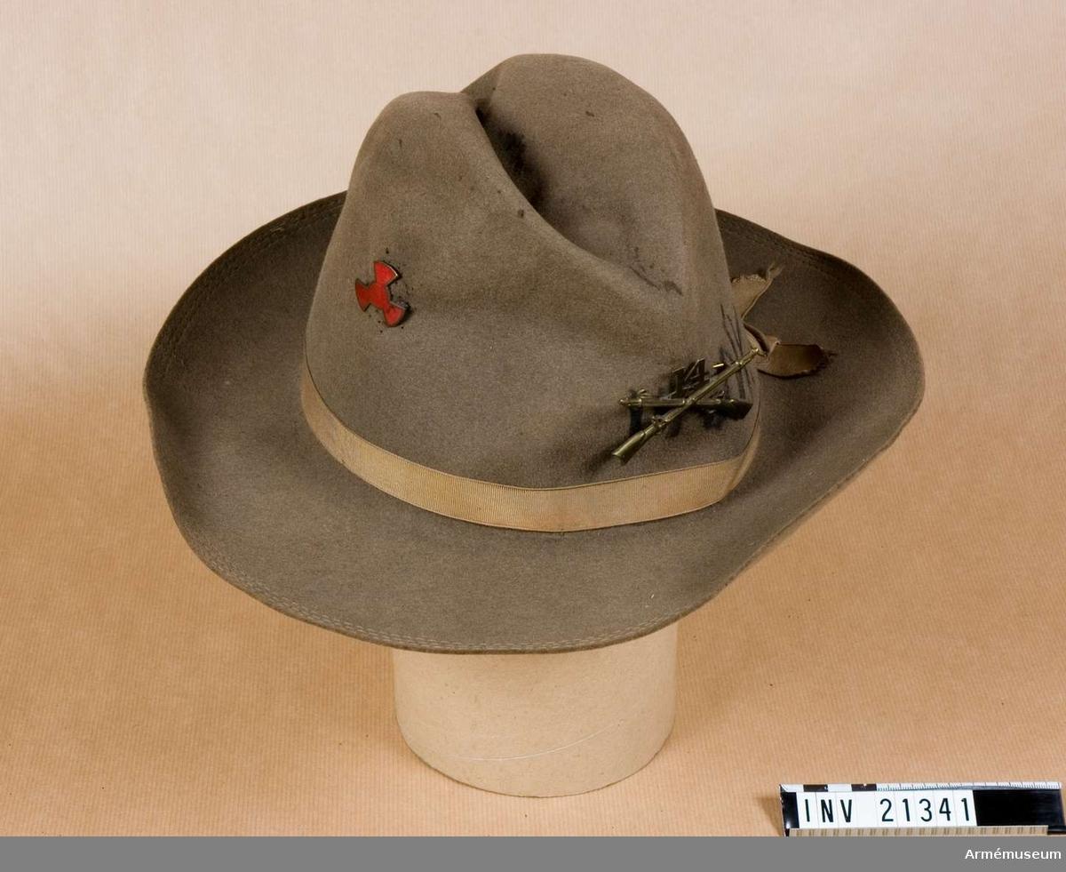 """Grupp C. Av filt i ljusbeige färg. Civil modell med längdveck i mitten och silkesband i samma färg, b:20 mm. På hattens framsida finns tecken - emblem för infanteri - av gulmetall: två gevär i kors med nummer """"14"""" ovanpå (infanteriregementsnummer """"14""""). På samma ställe finns på hatten handmålat nummer """"14"""" och bok- stäver """"IVR"""". Foder saknas, men finns svettrem av brunt läder. PÅ svettremmens baksida finns stämpel """"Waring Hat Co"""",  """"Controck Maj 17 1893"""" och """"N 216204"""". På hattens botten finns bokstäver och märken """"V"""" och några andra tecken och en liten pappersetikett med text """"7"""" (storlek). På hattens V sida finns regementstecken, emblem, av gulmetall och röd färg. LITT  Handbuch der Uniformkunde, professor Rickard Knötel, Hamburg 1937. Sida 400. År 1881 infördes i amerikanska armén mjukt grå hatt med längdveck. Sida 401. Bild Abb 156. Die Armée Vereinigten Staaten von Amerika 1872-1934. """"1903 d"""" - Officer i mjuk filthatt. Armeen album III. Die Armée Vereinigte Staaten Amerika. Bilaga sidan 4. """"Offiziere"""" i """"Dienstuniform im Felde"""" - i sam- ma hatt. Sida 11. Offiziere. Infanteritecken med två gevär i kors med regementsnummer ovanpå. Liknar detta tecken.Enl kapten Granberg."""