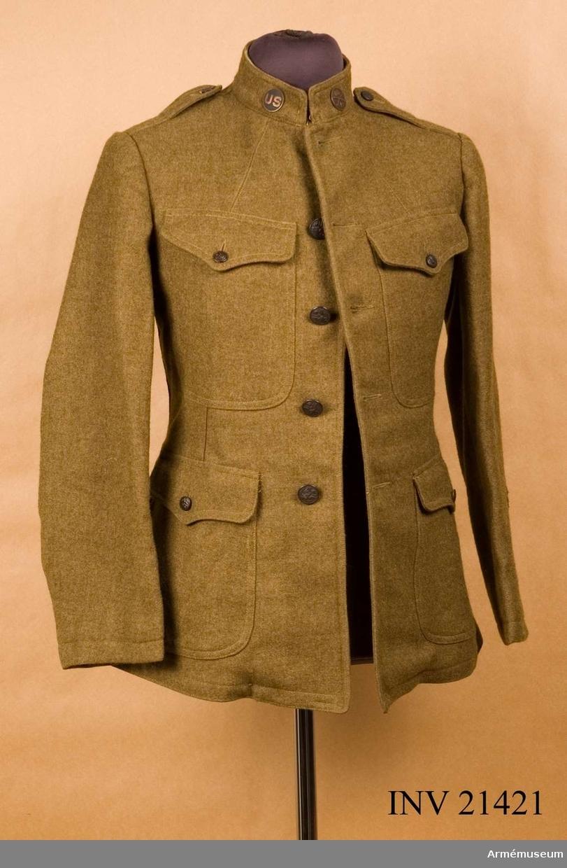 Grupp C I. Ur uniform för menig under 1. världskriget. Består av vapenrock, byxor, overseas hat, skjorta, livrem, väska, gasmask, damasker, ammunitionsbälte, muddar, strumpor, identitetsbricka, plös, stålhjälm. Angående märken och knappar på vapenrocken: Knappen på rockens V krage är symnbolen för American Expedi- tionary Forces (AEF) som uppstod i och med den amerikanska krigsförklaringen i april 1917. På V arm är två vinklar fast- sydda. Den övre uppåtgående vinkeln är röd och visar att sol- daten är en PRIVATE FIRST CLASS. Den nedre nedåtgående vinkeln är gul guld och visar att solda- ten har deltagit i strid i sex månader. Överst på V arm är ett runt märke med svart bakgrund och gult kors fastnålat. Detta märke som är symbol för 33 infanteri- divisionen är troligen inte samhörande med denna uniform. Tradition att på V arm ha divisions- eller regementsmärke upp- stod i slutskedet av första världskriget och rörde främst främst. 1. Infanteridivision (Big Red One) som fick bära en stor röd etta på V armen som utmärkningstecken. På H arm är tre vinklar fastnålade. Tre vinklar, uppåtgående, är tecknet för sergeant. Då tecknet för PRIVAT FIRST CLASS är fastsytt på vänsterarmen är det troligt att också detta tecken är icke sammanhörande. Dessa två tecken är därför borttagna nedstoppade i H bröstficka på vapenrocken. Uppgifter givna av överste Leo J Wecks arméattache US Embassy. LP 1986. Gåva av Museum Newport Artillery Company, P.O. Box 14 Newport R I, USA.