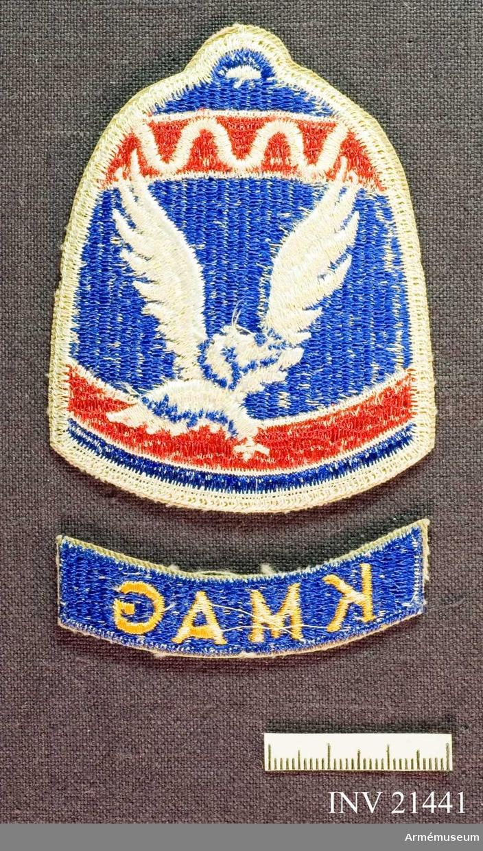 """Samhörande gåva: 21437-51, 22351-2, uniformsemblem.Emblem, Korean Military Advisory Group. Grupp C I. För amerikansk trupp som deltog i striderna i Korea 1950-53. KMAG = Korean Military Advisory Group, bars av den personal som ingick i instruktörstrupperna - mest från US Forces - och som utbildade de sydkoreanska förbanden. Emblemet är en sydkoreansk tempelklocka med koreanska örnen infälld. Textbandet under """"Klockan""""."""