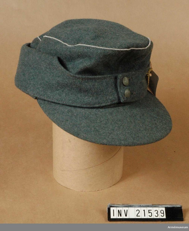 Grupp C. Av gröngrått kläde. Nedvikbara bräm som knäpps ihop framtill med 2 st gröna knappar. Rak skärm.  Snören av aluminium, officers kännetecken. LITT   Uniformen der Deutschen Wehrmacht von Eberhard Hettler. Berlin 1939.