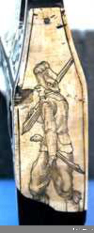 Grupp E II a.  Pipan är åttkantig. Siktet är rörformigt och av mässing samt slutar baktill i ett huvud med turban.    Luntlåsets bleck är i ändarna liksom även hanen prytt med gravyr.  Stocken är rikt inlagd med elfenben och pärlemor men ganska mycket av inläggningen har fallit bort.   Bakplåten är av ben och skadad samt prytt med bilder av en skytt.   Varbygeln och laddstocken fattas.