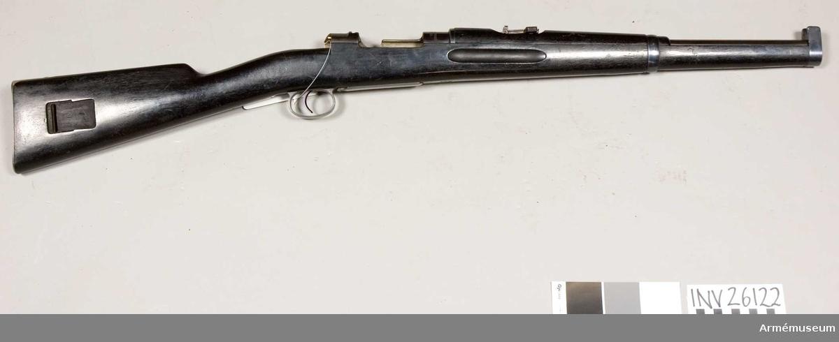 """Grupp E II f. Märkt """"Karl Gustavs stadsgevärsfaktori 1898 (i Eskilstuna)"""".  Stocken svartbetsad. Mausers system. 6,5 mm. För kammarskjutning. På lådans vänstra sidan står:""""K"""", tillverkn.nr. 99. Se AM 4596."""