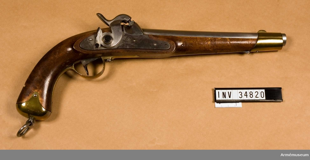"""Grupp E III b.  Studsarepistol med slaglås. Använd vid skjutförsök 1845-1846.  Fyra räfflor. Loppets rel. l:17 kal. Pipan är blank och rund, men har baktill på var sida en platt. Baktill på högra platten är den med eldskärm försedda snäckan fastsmidd. Ett båtformigt mässingskorn är fastlött 2,8 cm. bakom mynnigen och på svansskruvsstjärten sitter framtill ett ståndsikte. På pipans undersida 8 cm. framför bakänden finnes ett häfte. Längst bak på pipans undersida är inslaget CGW och P. Låset har platt, med höga kanter försett bleck och varhake samt liknar mycket låset till 1845 års infanterigevär, men är mindre. På utsidan av låsblecket är inslaget """"Carl Gustaf Stad"""" och ett krönt C. På bleckets insida står IFL.  Stocken är av brunbetsad björk och påminner om m/1820, men har mera krönt kolv än sistnämda modell. Framstocken har ej laddstocksränna. Pipan fasthålles i stocken dels genom den nedifrån insatta korsskruven, dels genom näsbandet och dels genom ett stift, som går genom häftet på pipan. Varbygeln är av mässing och, liksom näsblecket, av m/1820. Det sistnämda fashålles av en på stockens undersida bakom bandet liggande, med tapp försedd bandfjäder.  Sidblecket är av samma typ som på infanterigevär m/1840 och m 1845 samt infällt i jämnhöjd med stockens yta. Mot ändarna och på mitten är det är det utvidgat och den bakre änden är svängd uppåt.Kappan är av mässing, har korta, upptill avrundade flikar och fasthålles genom en skruv, som går genom flikarna och kolven. Genom kappans centrum går en skruv, som har klotrunt, av ett hål genombrutet huvud, i vilket en rörlig järnring är inpassad. Anslagsjärnet är av samma typ som på pistoler m/1820 och fasthålles av tre uppifrån isatta skruvar, men den fjärde, nedersta skruven fasthåller också varbygelns bakre långa arm samt går genom kolven och är inskruvad i häftjärnet. Alla skruvar har blånade huvud. J Alm 1941.  Samhörande nr 34820-1, pistol, löskolv. I par med 34822."""