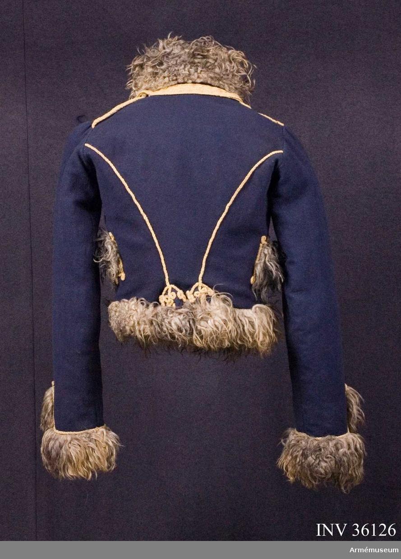Grupp C I. Ur uniform för manskap vid Skånska husarregementet; 1816. Består av dolma, päls, byxor, mössa, plym, tillbehör, halsduk, handskar, skärp, stövlar, sporrar, kartusch med rem, sabelkoppel, taska med remmar, sabelhandrem.