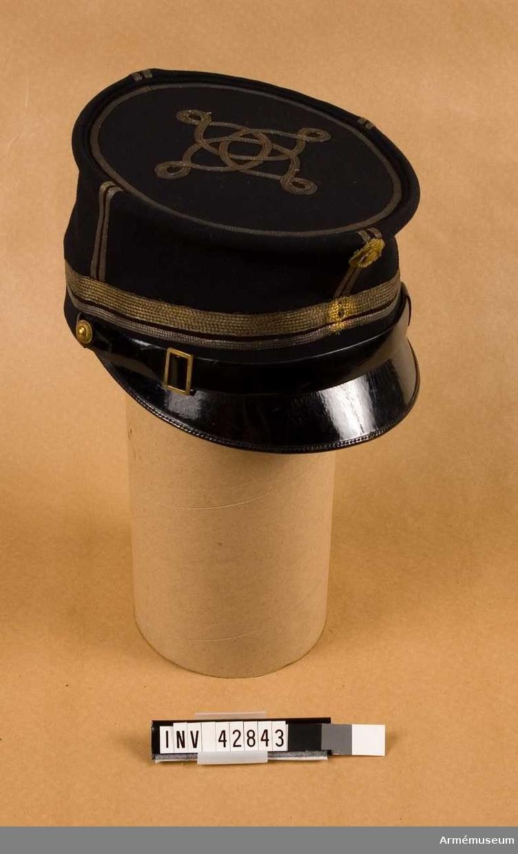 Grupp C I. Mössa m/1865-86 med majors gradbeteckning. Ur uniform (daglig dräkt) för officer vid Svea artillerireg. Består av kollett, ridbyxor, mössa, kappa, ridstövlar, sporrar.