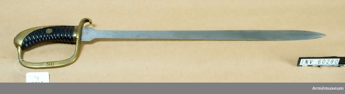 Grupp D II. Huggare för bevakningsmanskap vid fängelser. 1880-1900 ca.Huggaren överensstämmer helt med AM 60271. Klingan har inga synliga stämplar, som parerstångens undersida är baktill TLN inslaget och som handbygelns yttersidan står numret 50.