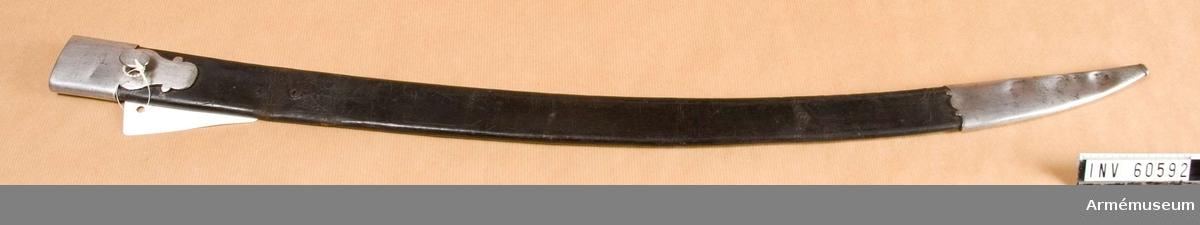 Grupp D II.  Baljan är av svart läder med två beslag av järn, den är till sin utformning lik en huggarbalja.  Beslagen består av munbleck och doppsko. Munblecket har på yttersidan en oval koppelknapp.