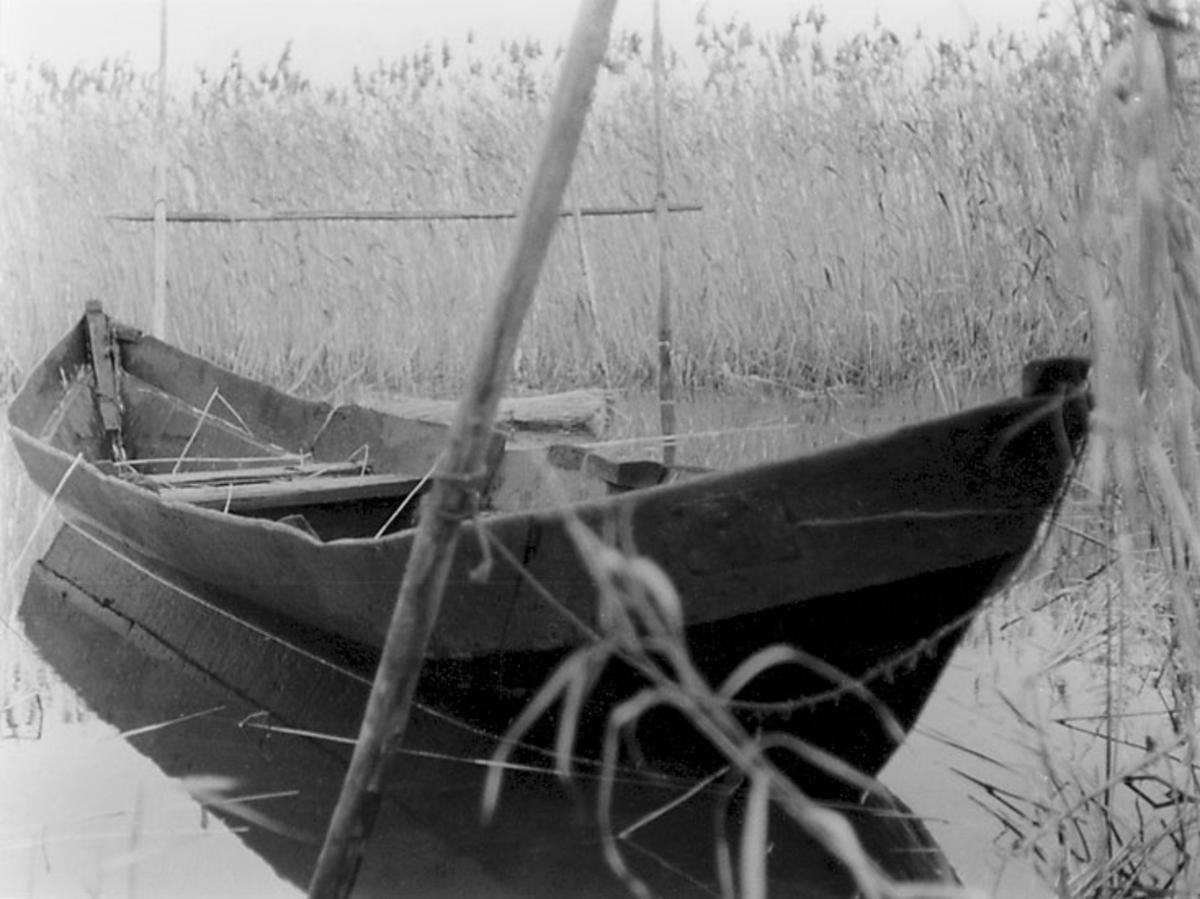 """Skrivet på baksidan: """"Bodenplankenboot ohne Steven. Kahn v. Garder See (Ostpreussen). 14.""""  Stämplat på baksidan: """"50.""""   Fotona är tagna mellan 1966-09-11 - 1966-09-17."""