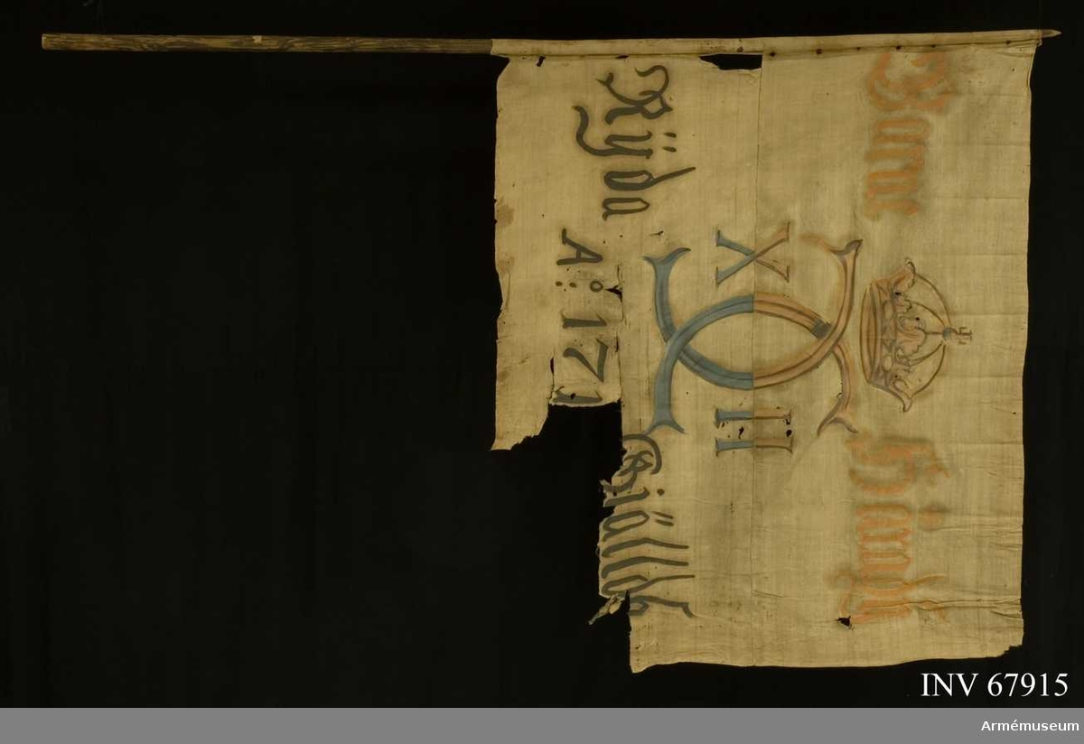 Duk: Tillverkad av enkel vit linnelärft, sydd av två horisontella våder.  Dekor:  Målad, endast från dukens utsida, Karl XII:s monogram dubbelt C med X-II på ömse sidor, krönt med sluten krona, i det övre fältet i gult och brunt, det nedre fältet i blått och svart. Text på ömse sidor om chiffret; upptill i gult, nedtill i svart.  Stång av trä. Spikar under ett linneband.