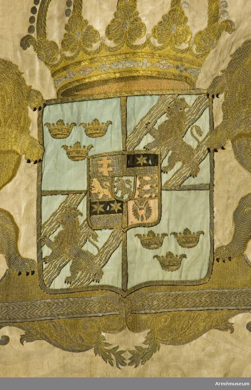 Duk: Tillverkad av dubbel, vit damast.   Dekor: På inre sidan broderat med guld Fredrik I:s namnchiffer - dubbelt F under sluten kunglig krona, palmkvistar, svenska riksvapnet Hessen-Kassel, i övre inre hörnet Karelens sköldemärke.  Stång: Tillserkad av furu, sexräfflad ovan greppet och förstärkt med tre järnskenor. Vitmålad med förgyllning.