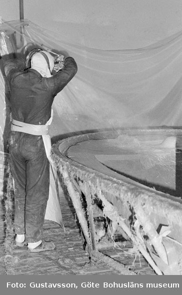 """Motivbeskrivning: """"Gullmarsvarvet AB, sputning av gelcoat och glasfiber på form. På bilden syns Ove Johansson."""" Datum: 19801031"""