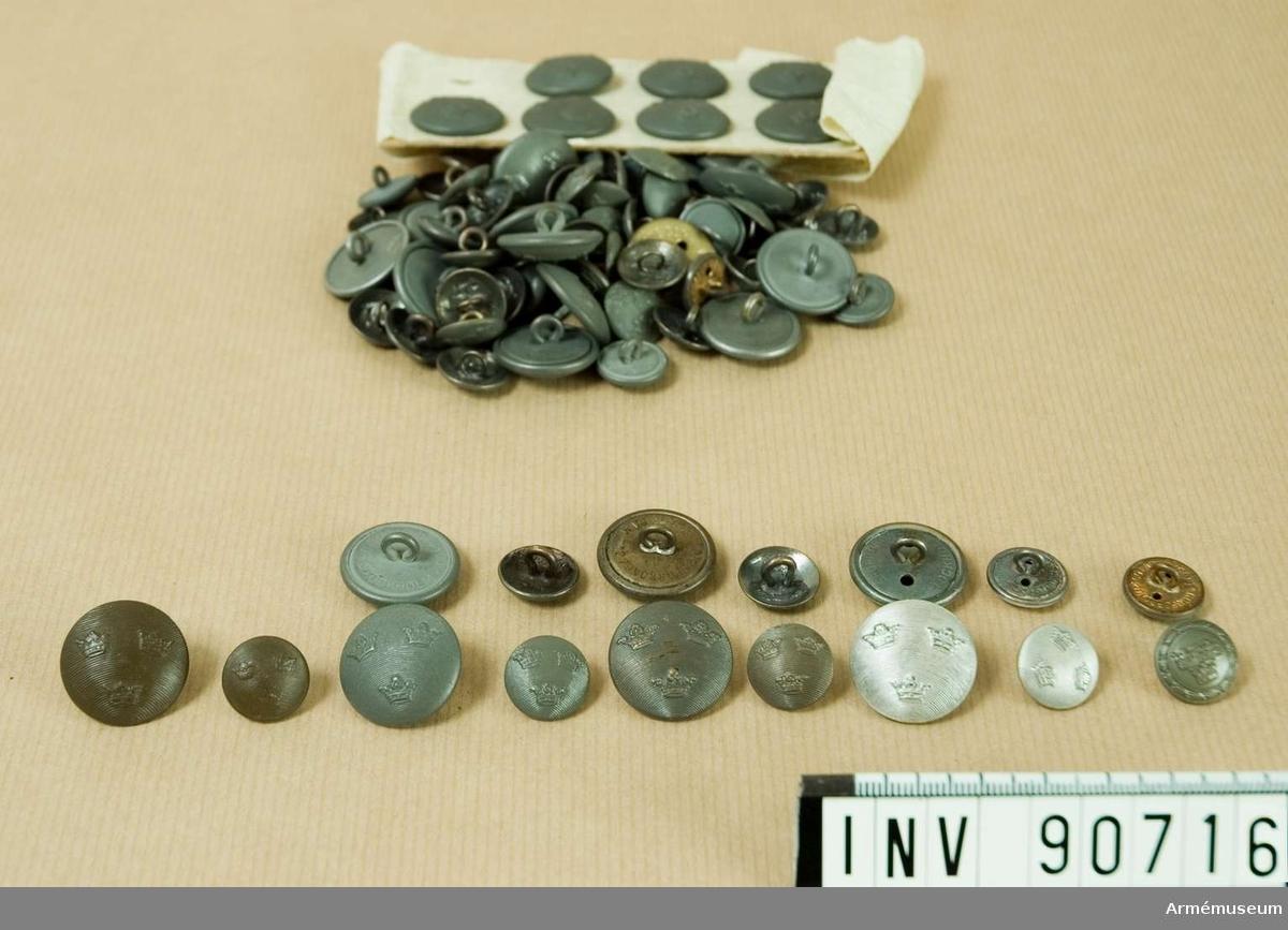 Låda med stort antal knappar av olika sorter. Bland annat grå bakelitknappar m/1939.
